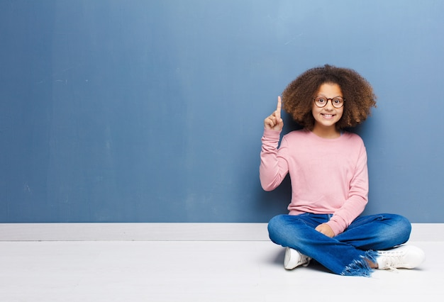Afro-américaine petite fille souriante joyeusement et joyeusement, pointant vers le haut avec une main pour copier l'espace assis sur le sol