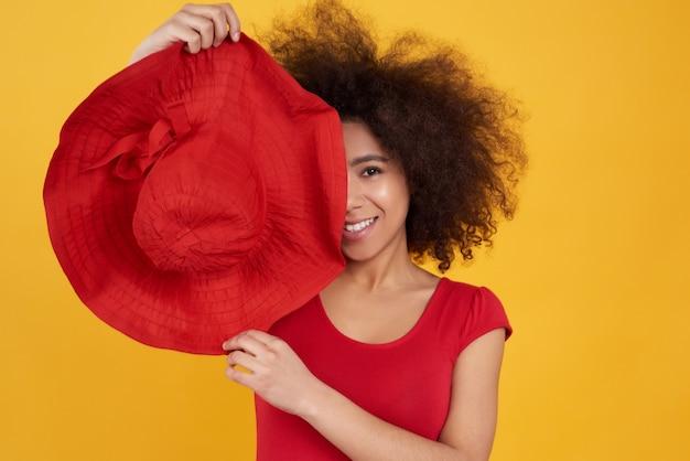 Afro-américaine avec pose de chapeau rouge isolé