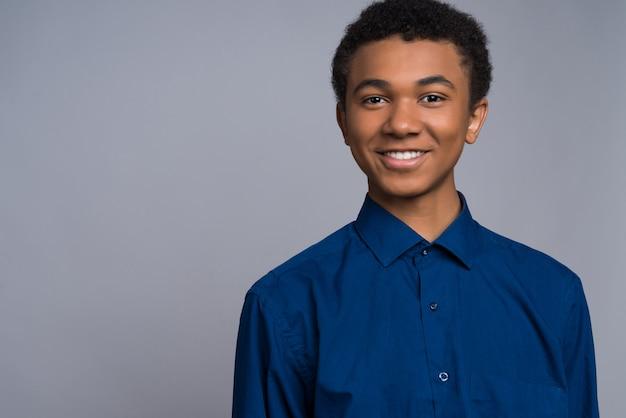 Afro american boy avec bonne humeur sourit devant la caméra.