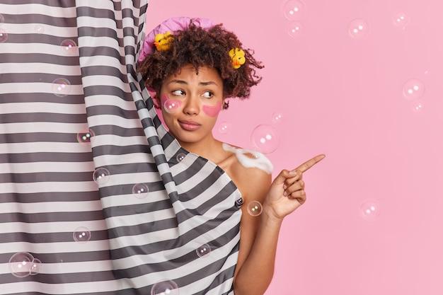 Afro american curly woman prend une douche dans la salle de bains applique du gel douche indique loin sur l'espace de copie se cache derrière un rideau isolé sur un mur rose avec des bulles de savon autour