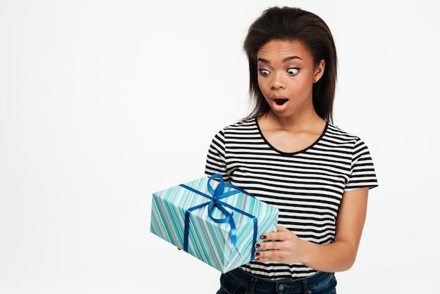 Afro american teenager woman holding et regardant la boîte actuelle