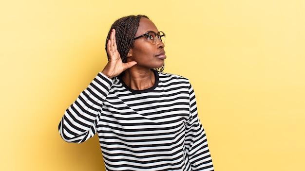 Afro black jolie femme à la recherche de sérieux et de curiosité, écoutant, essayant d'entendre une conversation secrète ou des potins, espionnant