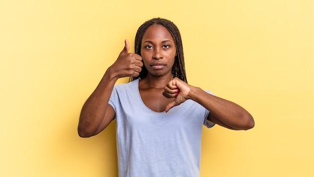 Afro black jolie femme se sentant confuse, désemparée et incertaine, pondérant le bien et le mal dans différentes options ou choix