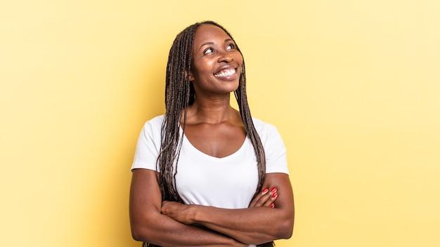 Afro black jolie femme se sentant heureuse, fière et pleine d'espoir, se demandant ou pensant, levant les yeux pour copier l'espace avec les bras croisés
