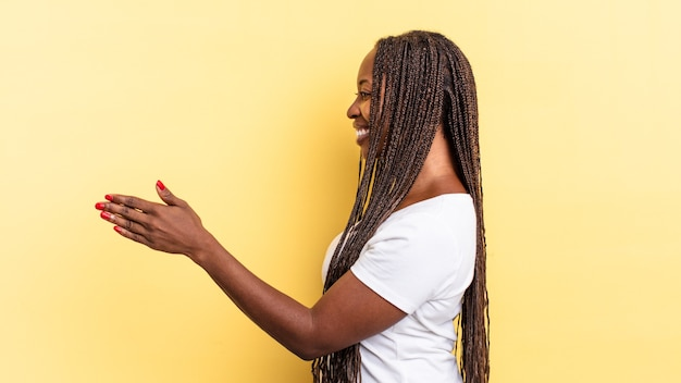 Afro black jolie femme souriante, vous saluant et offrant une poignée de main pour conclure un accord réussi, concept de coopération