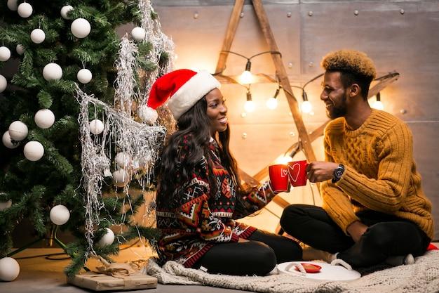Afro couple américain, boire du café par le sapin de noël