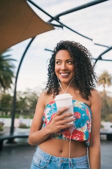 Afro femme écoutant de la musique tout en tenant une tasse de café