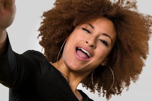 Afro femme prenant un selfie, visage agrandi