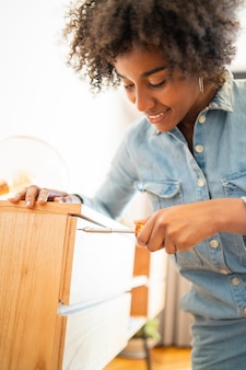 Afro femme réparant des meubles à la maison.