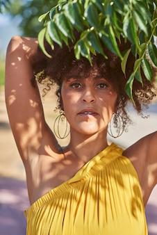 Afro femme tient quelques branches près de son visage. l'ombre des feuilles est projetée sur son visage. écologie, concept de la nature.