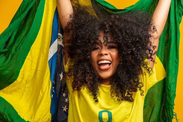 Afro girl acclamant l'équipe brésilienne préférée, tenant le drapeau national dans le mur jaune.