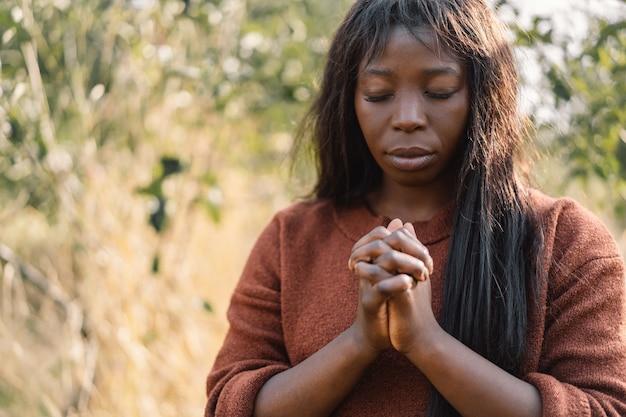 Afro girl aux yeux fermés, priant à l'extérieur