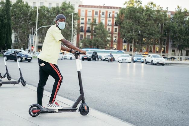 Afro homme avec masque chirurgical sur scooter électrique contre ville. il porte un t-shirt jaune et un jean noir. vue de côté.
