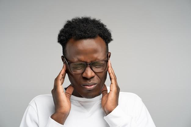 Afro homme se sentant mal de tête ou migraine massage des tempes épuisé par le surmenage sur fond gris