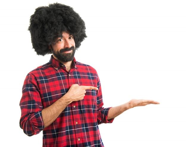 Afro homme tenant et pointant quelque chose