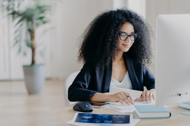 Une afro indépendante travaille à distance, écrit des informations, se concentre sur un écran d'ordinateur avec une expression ravie
