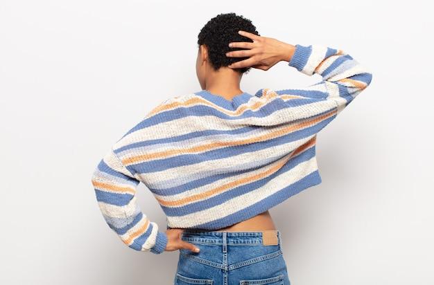 Afro jeune femme noire penser ou douter, se gratter la tête, se sentir perplexe et confus, vue de dos ou arrière