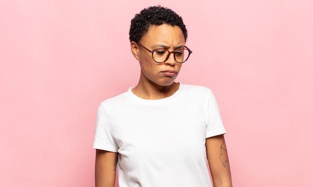Afro jeune femme noire se sentant triste, bouleversée ou en colère et regardant sur le côté avec une attitude négative, fronçant les sourcils en désaccord