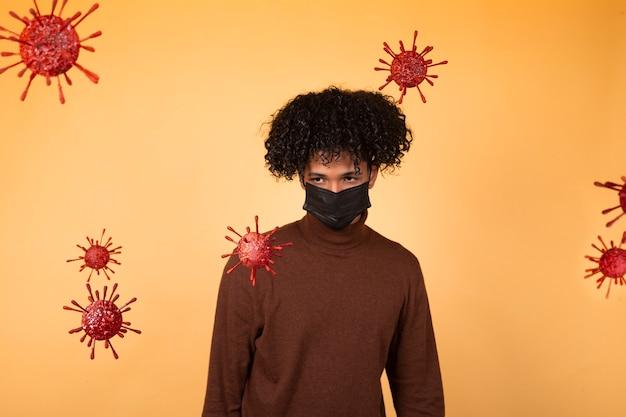 Afro jeune homme avec un masque médical sur fond jaune en regardant des molécules de bactéries. épidémie, virus, santé. copier l'espace