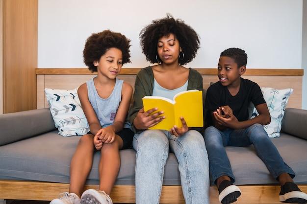 Afro mère lisant un livre à ses enfants.