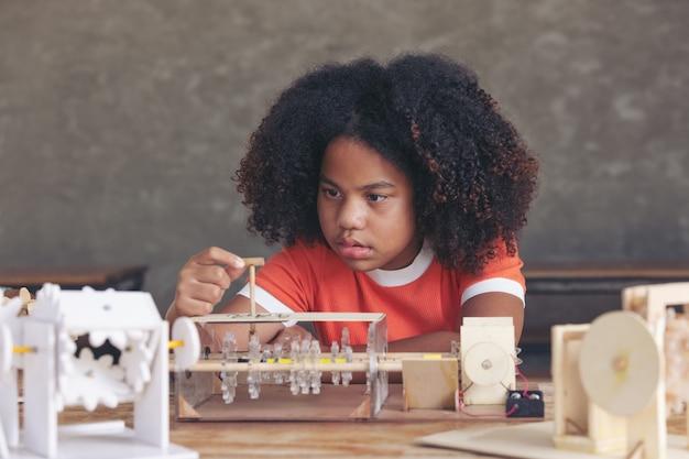 Afro teen girl cheveux bouclés en regardant les parties du modèle de robot de mécanisme de simulation en bois