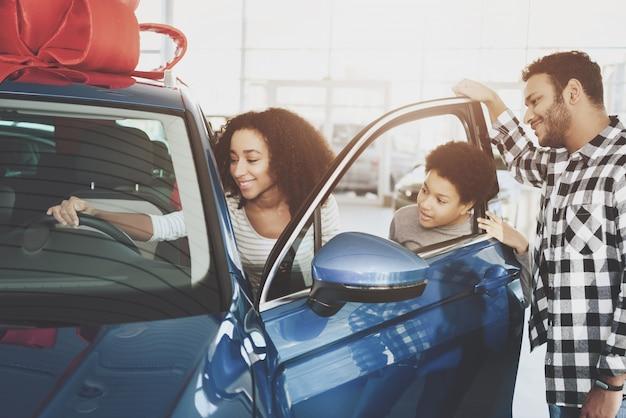 Afro woman prend la nouvelle voiture de luxe dans la salle d'exposition.
