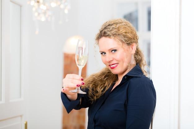 After hour - femme à la maison avec du vin mousseux