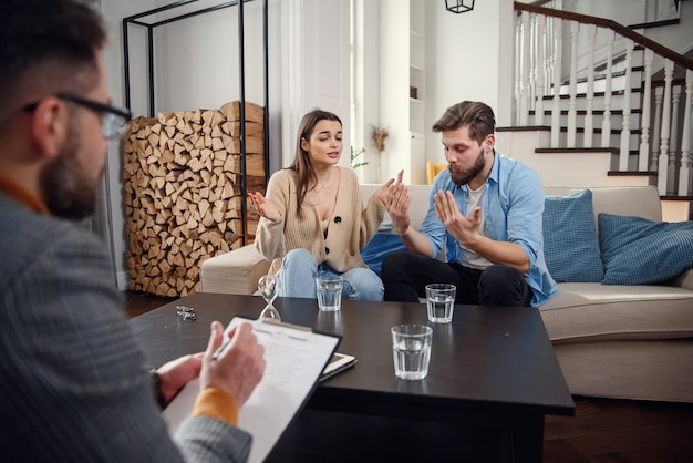 Agacé couple caucasien d'homme et femme ayant une conversation avec un psychologue sur la séance de thérapie dans la salle lumineuse.