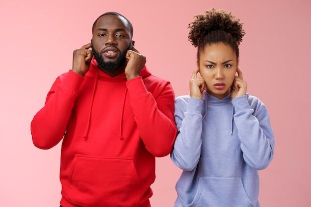Agacé, fatigué, couple, femme afro-américaine, homme, relation, épuisé, mutuellement, oreilles fermées, bouchon, index, fronçant les sourcils, regard irrité, entendre, terrible, déranger, bruit, debout, rose, fond