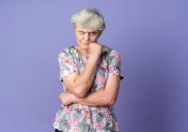 Agacé femme âgée met la main sur le menton avec impatience isolé sur mur violet
