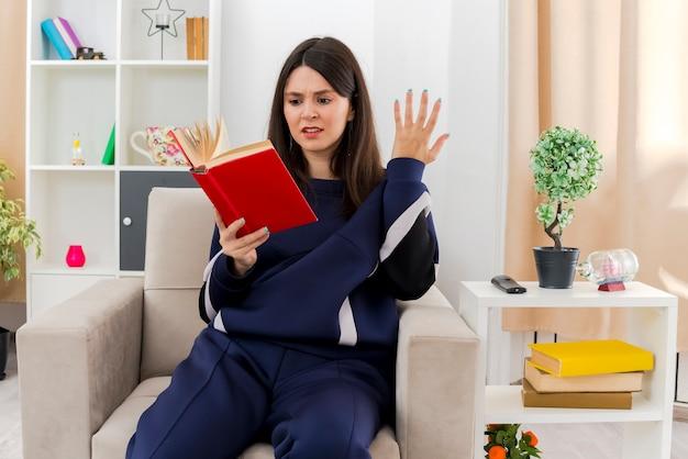 Agacé jeune femme assez caucasienne assise sur un fauteuil dans le salon conçu tenant et regardant livre et gardant la main en l'air