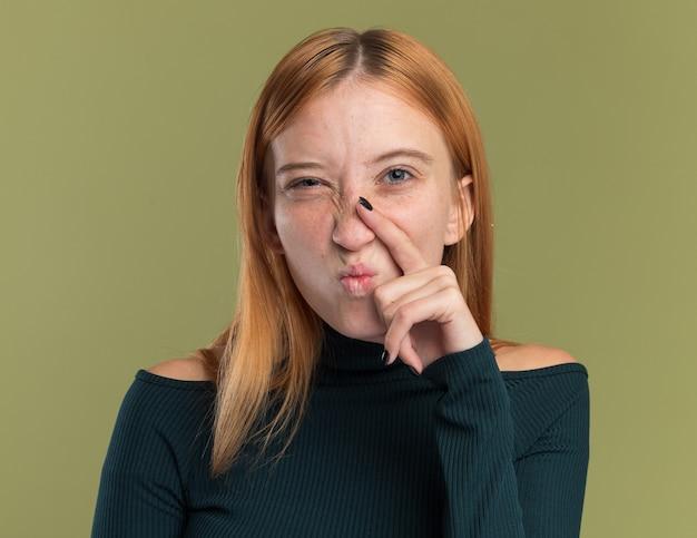 Agacé jeune fille rousse au gingembre avec des taches de rousseur met le doigt sur le nez et regarde la caméra sur le vert olive