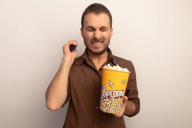 Agacé jeune homme caucasien tenant seau de pop-corn et télécommande montrant les dents avec les yeux fermés isolé sur fond blanc avec copie espace