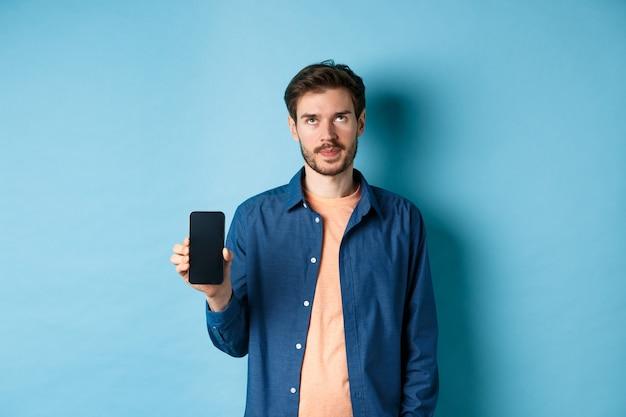 Agacé jeune homme montrant l'écran du smartphone vide et rouler les yeux dérangé, debout sur fond bleu.