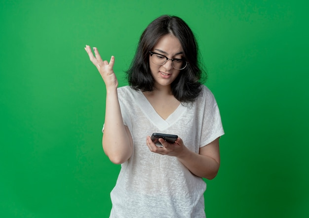Agacé jeune jolie fille caucasienne portant des lunettes tenant et regardant le téléphone mobile et en gardant la main dans l'air isolé sur fond vert avec espace copie