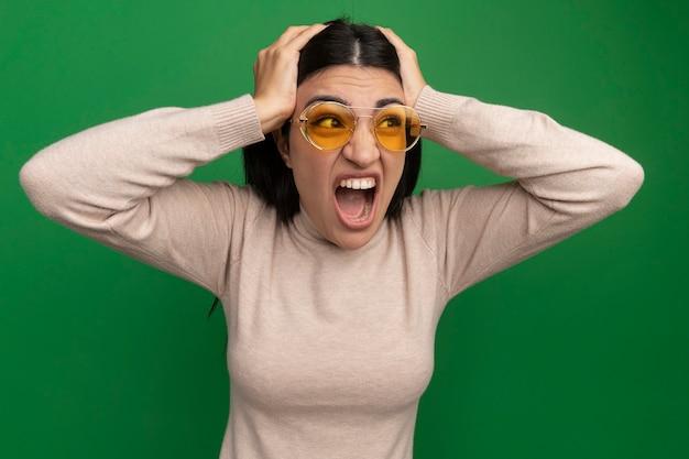 Agacé jolie femme brune à lunettes de soleil met les mains sur la tête et regarde côté isolé sur mur vert