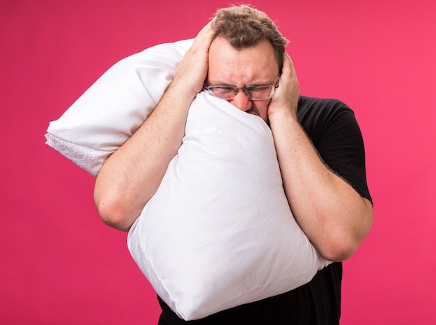 Agacé avec les yeux fermés un homme malade d'âge moyen étreint les oreilles couvertes d'oreillers avec les mains