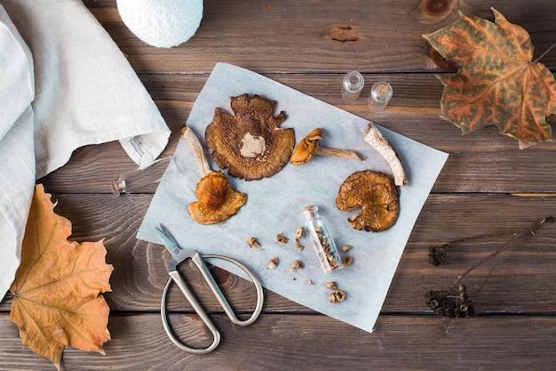Agarics mouches hachés séchés empilés dans un petit pot et champignons secs sur parchemin et ciseaux sur une table en bois. microdosage et médecine alternative. vue de dessus