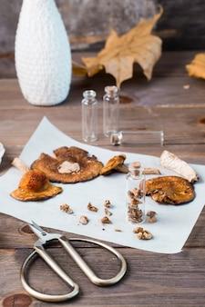 Agarics mouches hachés séchés empilés dans un petit pot et champignons secs sur parchemin et ciseaux sur une table en bois. microdosage et médecine alternative. vue verticale