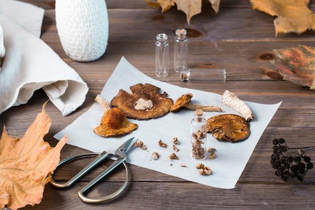Agarics mouches hachés séchés empilés dans un petit pot et champignons secs sur parchemin et ciseaux sur une table en bois. microdosage et médecine alternative.