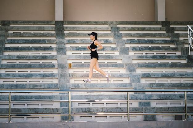 D'âge moyen belle femme asiatique sportive athlète de coureur en plein air courant sur les escaliers du stade mode de vie actif et sain.