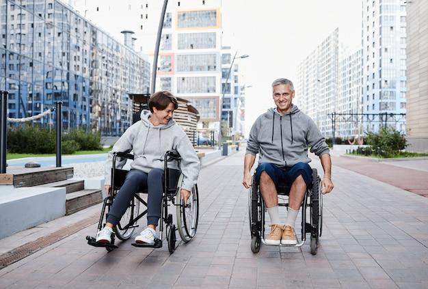 D'âge mûr avec un handicap parlant et souriant tout en roulant en fauteuil roulant le long de la rue