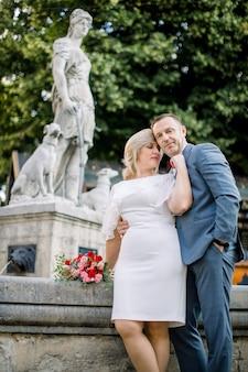 D'âge mûr s'embrassant devant une fontaine d'eau de la ville, regardant ailleurs et rêvant