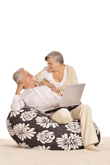 D'âge mûr se détendre à la maison avec un ordinateur portable sur un blanc