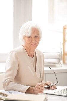 Agé de succès féminin chef d'entreprise en costume élégant blanc assis par lieu de travail devant un ordinateur portable pendant le travail
