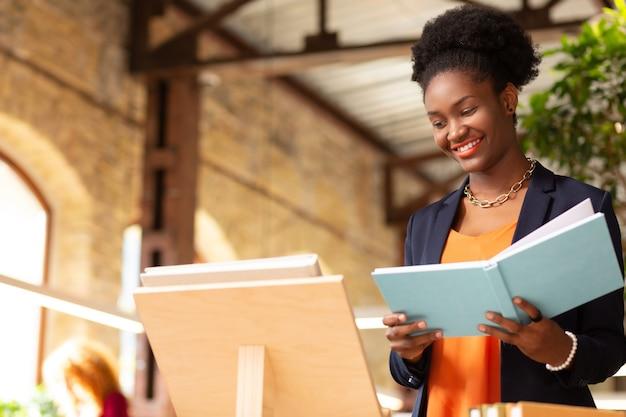 Agence d'édition. femme à la peau foncée bouclée souriant tout en travaillant dans une agence d'édition