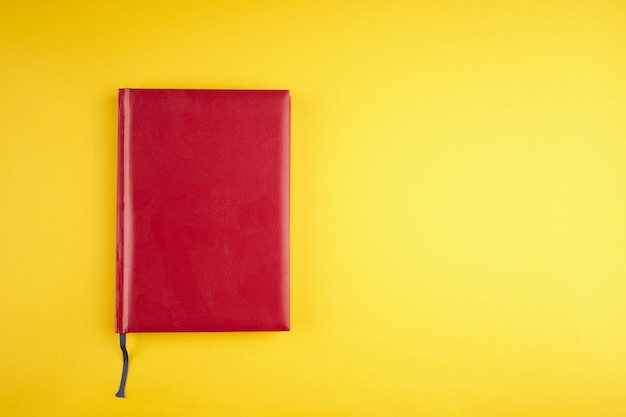 Agenda en cuir rouge vierge sur fond tendance jaune. copie espace. vue de dessus