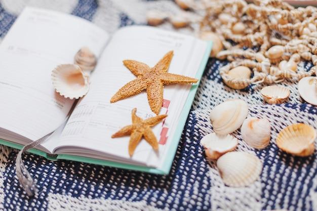 Agenda ouvert avec les étoiles de mer et les coquilles