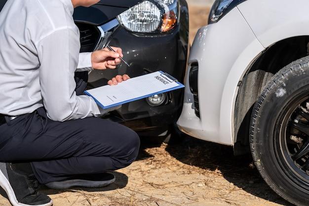 Agent d'assurance inspectant la voiture endommagée évaluée, vérifiant et signant le formulaire de réclamation d'assurance du rapport