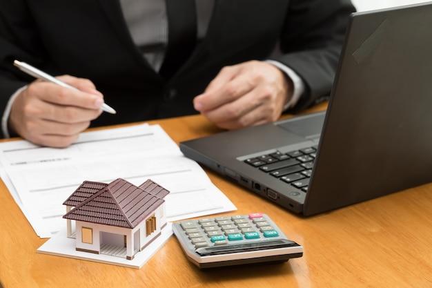 L'agent de la banque calcule les taux d'intérêt prêt hypothécaire mensuel pour l'acheteur